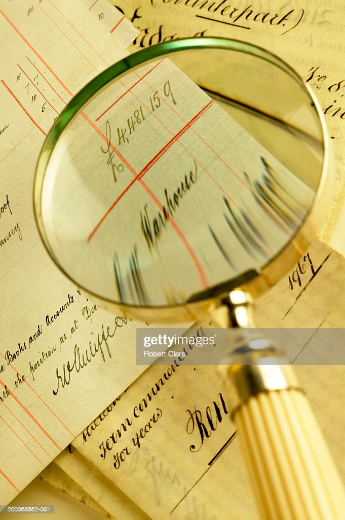Magnifying glass poised over antique handwritten balance sheets : Stock Photo