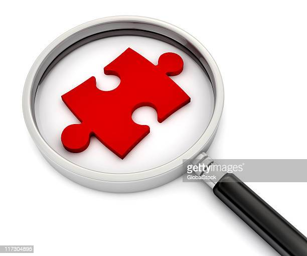 Magnifying glass with a red puzzle piece under it