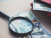 Magnifying glass with dollars