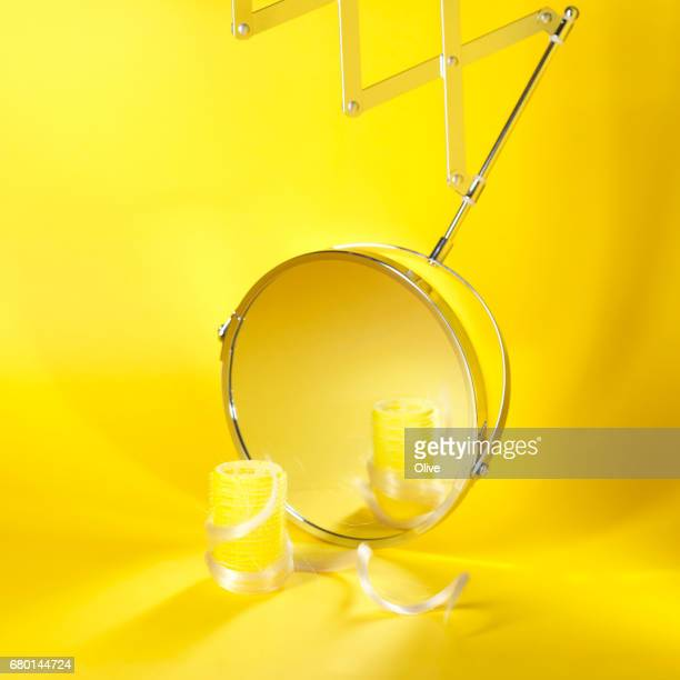 magnifying mirror on yellow background with roller