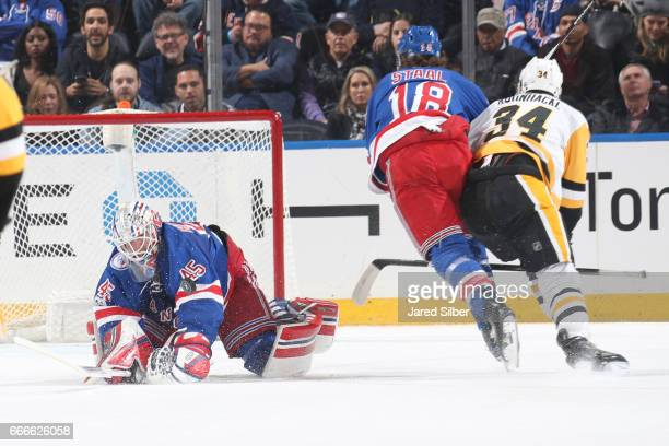 Magnus Hellberg of the New York Rangers dives out to knock the puck away as Marc Staal defends against Tom Kuhnhackl of the Pittsburgh Penguins at...