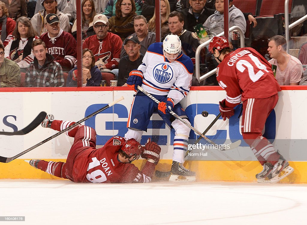 Magnus Paajarvi #91 of the Edmonton Oilers battles for the loose puck with <a gi-track='captionPersonalityLinkClicked' href=/galleries/search?phrase=Shane+Doan&family=editorial&specificpeople=201614 ng-click='$event.stopPropagation()'>Shane Doan</a> #19 and <a gi-track='captionPersonalityLinkClicked' href=/galleries/search?phrase=Kyle+Chipchura&family=editorial&specificpeople=879784 ng-click='$event.stopPropagation()'>Kyle Chipchura</a> #24 of the Phoenix Coyotes at Jobing.com Arena on January 30, 2013 in Glendale, Arizona.