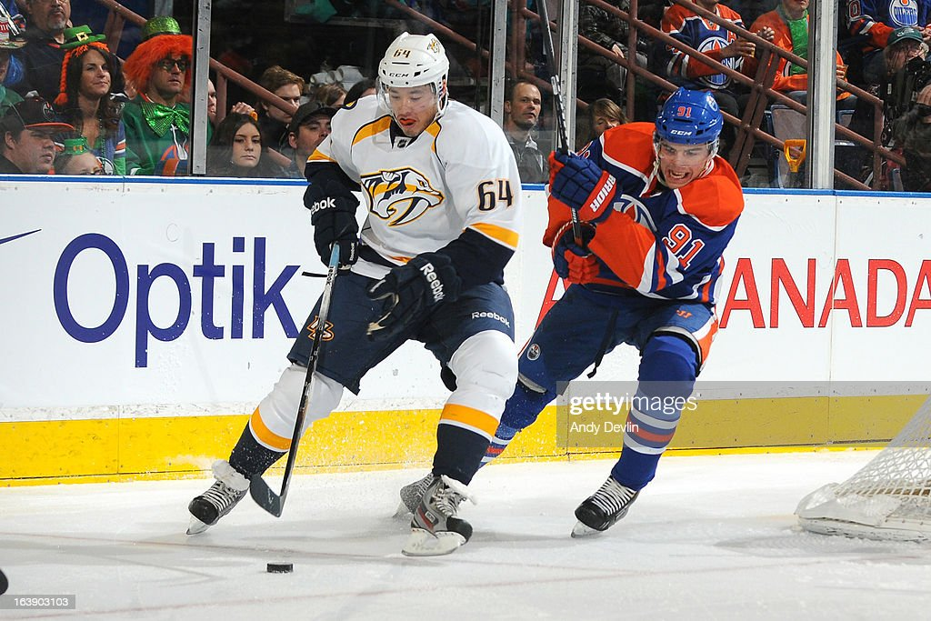 Magnus Paajarvi #91 of the Edmonton Oilers battles for the puck against Victor Bartley #64 the Nashville Predators on March 17, 2013 at Rexall Place in Edmonton, Alberta, Canada.