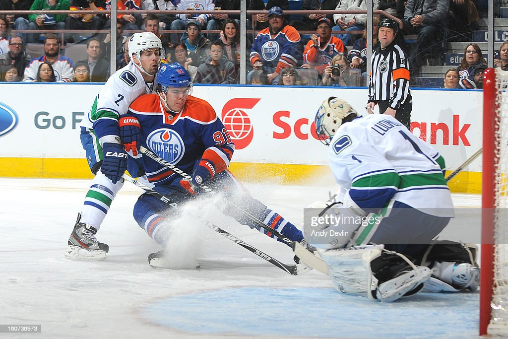 Magnus Paajarvi #91 of the Edmonton Oilers takes the puck hard to the net against <a gi-track='captionPersonalityLinkClicked' href=/galleries/search?phrase=Dan+Hamhuis&family=editorial&specificpeople=204213 ng-click='$event.stopPropagation()'>Dan Hamhuis</a> #2 and it stopped by <a gi-track='captionPersonalityLinkClicked' href=/galleries/search?phrase=Roberto+Luongo&family=editorial&specificpeople=202638 ng-click='$event.stopPropagation()'>Roberto Luongo</a> #1of the Vancouver Canucks on February 4, 2013 at Rexall Place in Edmonton, Alberta, Canada.