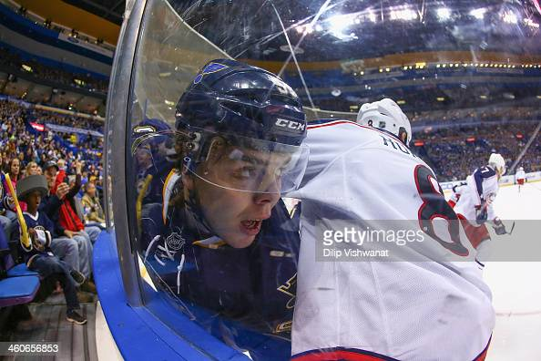 Magnus Paajarvi of the St Louis Blues is pinned against the boards by Nathan Horton of the Columbus Blue Jackets at the Scottrade Center on January 4...