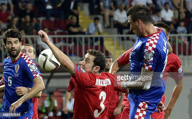 Magomed Mirzabekov of Azerbaijan vies for a ball with Mario Mandzukic of Croatia during the UEFA Euro 2016 qualifying football match between...