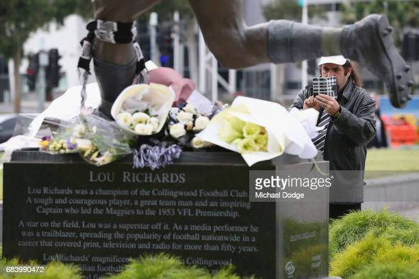 Magpies fans take photographs of the Lou Richards statue after the Lou Richards State Funeral Service at St Paul's Cathedral on May 17 2017 in...