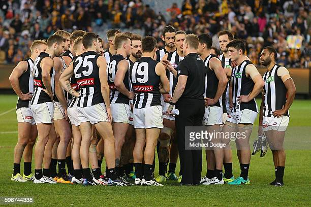 Magpies head coach Nathan Buckley speaks to his players after their defeat during the round 23 AFL match between the Hawthorn Hawks and the...