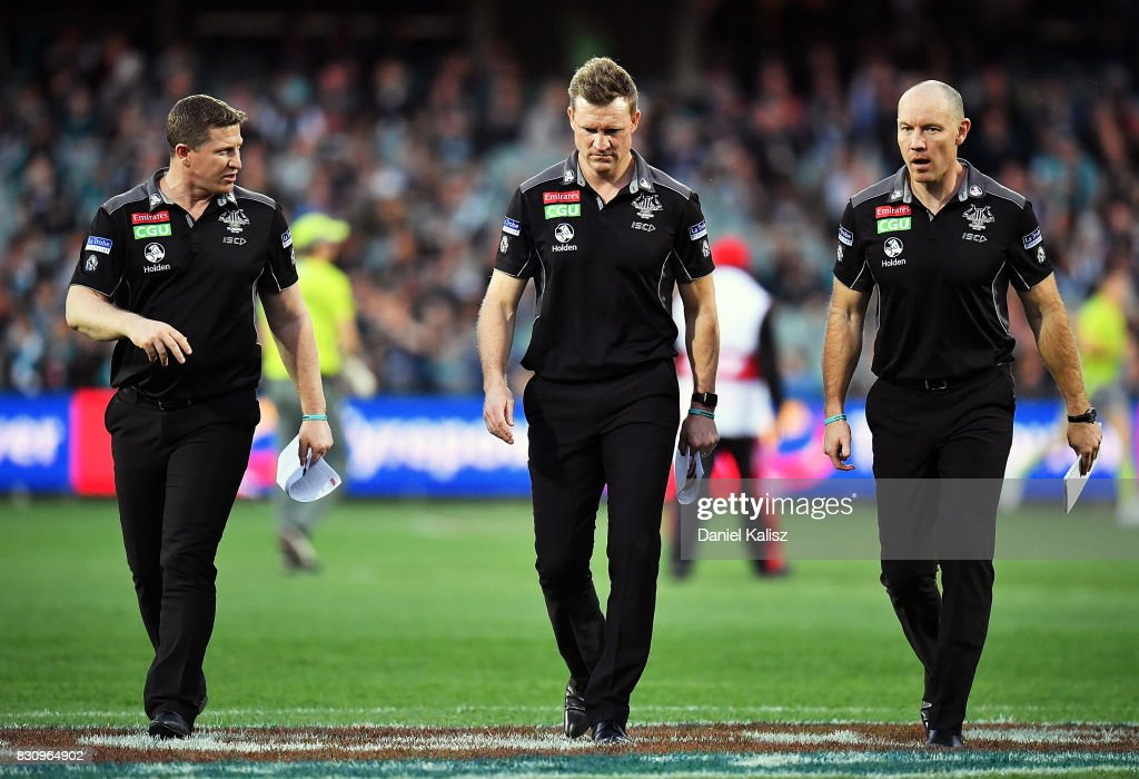 Magpies midfield coach Scott Burns, Magpies head coach Nathan Buckley and Magpies assistant coach Brenton Sanderson walk from the field during the round 21 AFL match between Port Adelaide Power and the Collingwood Magpies at Adelaide Oval on August 13, 2017 in Adelaide, Australia.