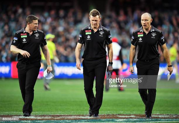 Magpies midfield coach Scott Burns Magpies head coach Nathan Buckley and Magpies assistant coach Brenton Sanderson walk from the field during the...