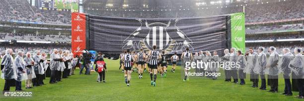Magpies players head to their banner marking 125 year celebrations during the round seven AFL match between the Collingwood Magpies and the Carlton...