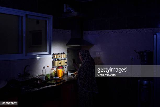 Maha Zant makes tea by cell phone light at her home in the AlZahra district on July 23 2017 in Gaza City Gaza For the past ten years Gaza residents...