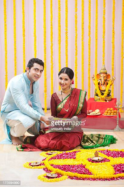 Maharashtrian couple making flower rangoli during ganesh chaturthi festival