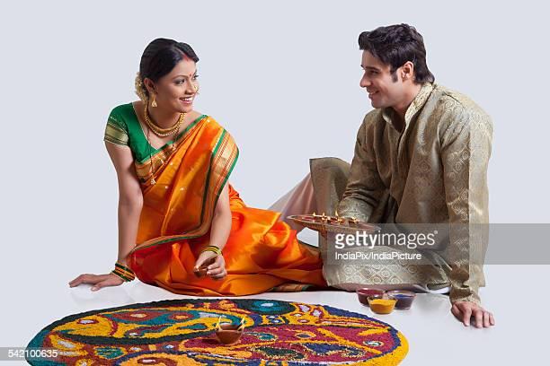 Maharashtrian couple placing diyas on rangoli