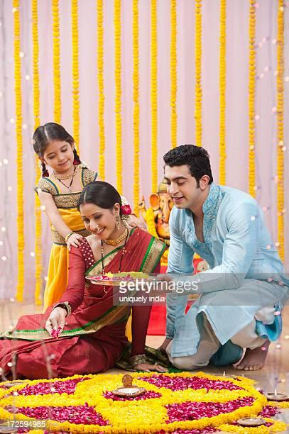 Maharashtrian family making flower rangoli during ganesh chaturthi festival