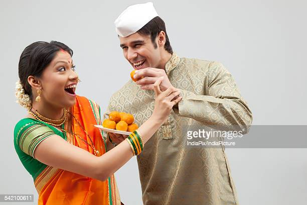 Maharashtrian man trying to feed woman a laddoo