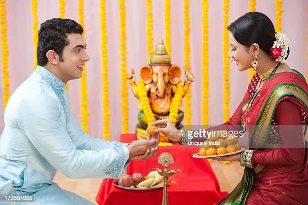 Maharashtrian woman giving prasada to her husband during ganesh chaturthi festival
