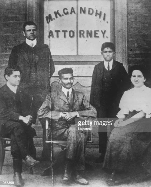 Mahatma Gandhi when he was practising as an attorney in South Africa He is seated in front of a window bearing his name on the left is H S L Polak...