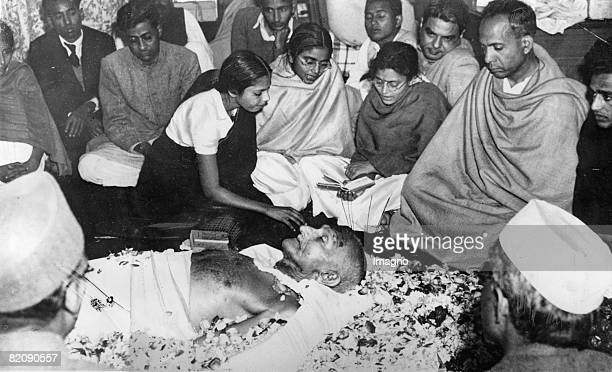 Mahatma Gandhis laying out in new Delhi after his assasination A nice lays flowers down Photograph 1948 [Mahatma Gandhi wird nach seiner Ermordung in...