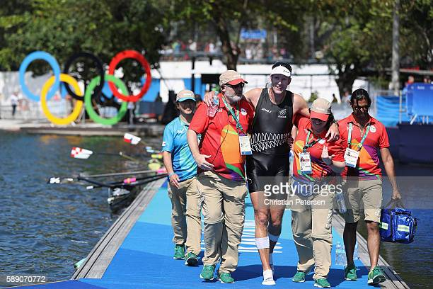 Mahe Drysdale of New Zealand is helped by volunteers after winning the gold medal in the Men's Single Sculls on Day 8 of the Rio 2016 Olympic Games...