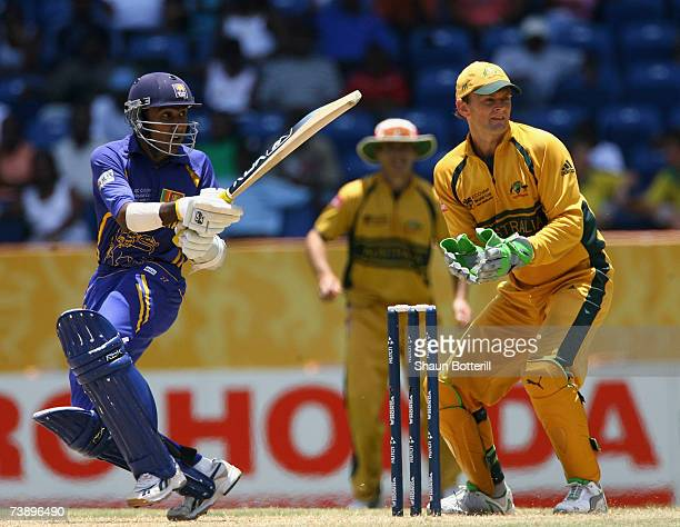 Mahela Jayawardene of Sri Lanka plays a shot as Adam Gilchrist of Australia looks on during the ICC Cricket World Cup 2007 Super Eight match between...