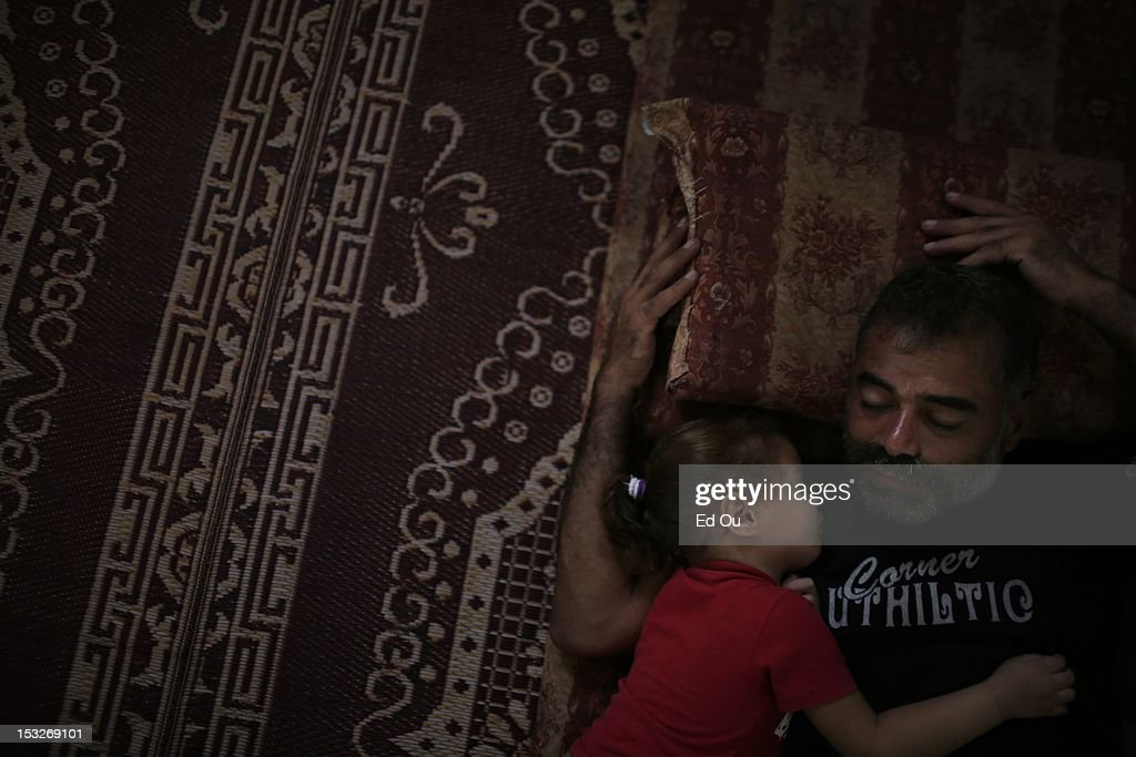 Maher Alghora, 41, sleeps with his daughter Sharouk in their makeshift house in Gaza's Forgotten Neighborhood on Sept. 6, 2012. A United Nations report issued last week questioned whether Gaza will be 'a liveable place' in 2020, citing shortages of food, clean water, electricity, jobs, hospital beds and classrooms amid an exploding population in what is already one of the most densely populated patches of Earth. The Forgotten Neighborhood, where about 40 families totalling 200 people have settled over the past four years near a municipal slaughterhouse in southern Gaza City, is an extreme case: the nicer homes are made of cinder blocks, or even stone slabs left from the security wall before Israel's disengagement, while others live in tents of rusty zinc sheets with branches for roofs.