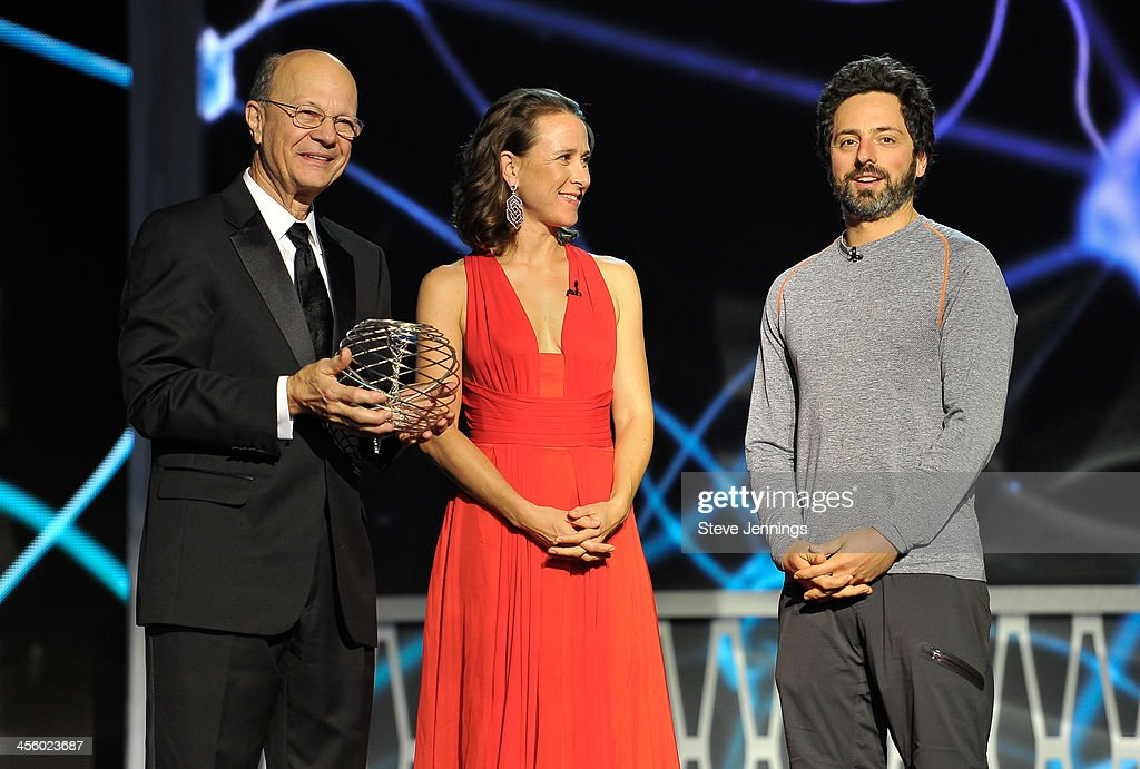 Mahlon DeLong (L) is awarded by presenters Anne Wojcicki and Sergey Brin at the 2014 Breakthrough Prizes Awarded in Fundamental Physics and Life Sciences Ceremony at NASA Ames Research Center on December 12, 2013 in Mountain View, California.