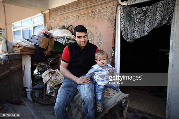Mahmad Siketa a refugee from Idlib in Syria poses for a photograph with one of his children outside the room he shares with his family on March 24...
