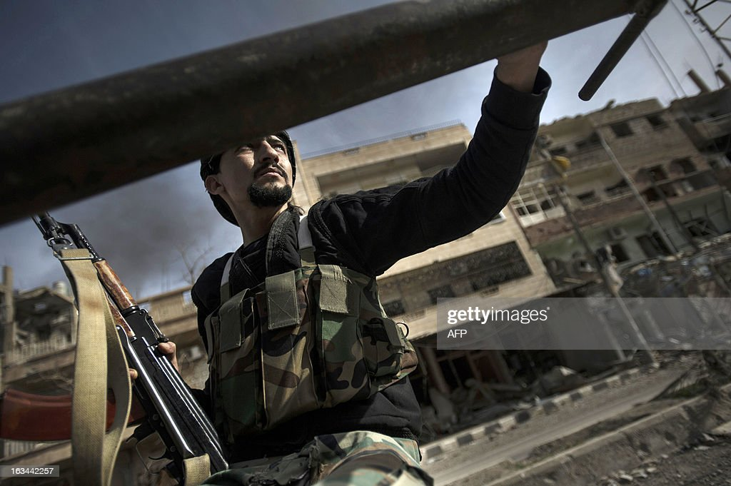 RODRIGUEZ - Mahmoud, a free Syrian army fighter and member of a mobile tank hunting unit, moves with an SPG rocket from one front line to another during ongoing clashes with regime forces on February 28, 2013 in Deir Ezzor. Once a thriving hub of Syria's oil industry, Deir Ezzor is now a ghost town of only a few thousand people struggling tenaciously to hang on against the odds after most of its people fled. AFP PHOTO ZAC BAILLIE
