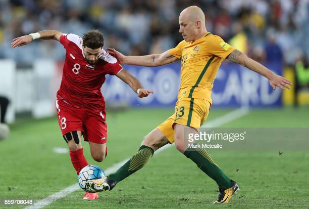 Mahmoud Al Mawas of Syria and Aaron Mooy of Australia compete during the 2018 FIFA World Cup Asian Playoff match between the Australian Socceroos and...