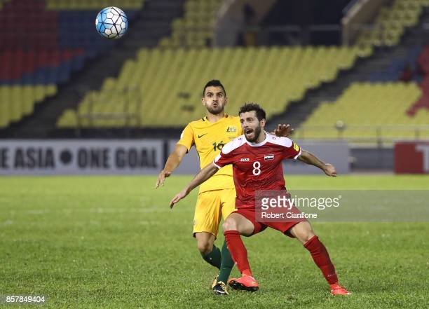 Mahmoud Almawas of Syria gets the ball ahead of Aziz Behich of Australia during the 2018 FIFA World Cup Asian Playoff match between Syria and the...