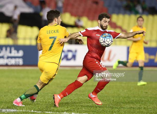 Mahmoud Almawas of Syria is pressured by Mathew Leckie of Australia during the 2018 FIFA World Cup Asian Playoff match between Syria and the...