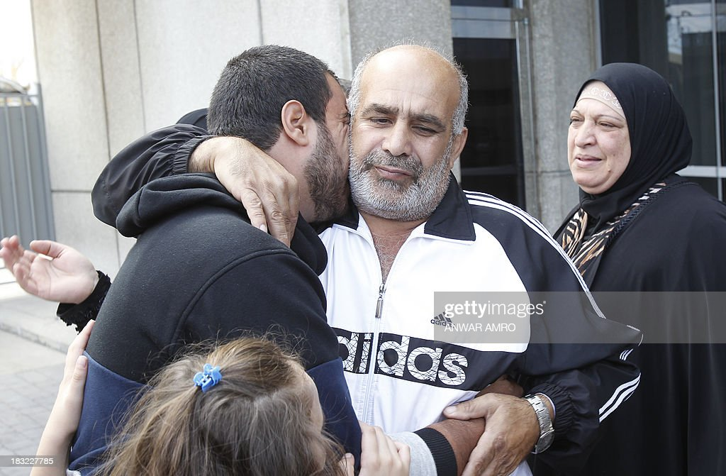 Mahmoud Bahri (L), a Lebanese survivor of the migrant shipwreck in Indonesia last week, is welcomed by relatives as he arrives at Beirut airport on October 6, 2013. Lebanese asylum-seekers who died when a boat sank off Indonesia were the victims of people smugglers who prey on them and Syrian refugees seeking to better their lives.