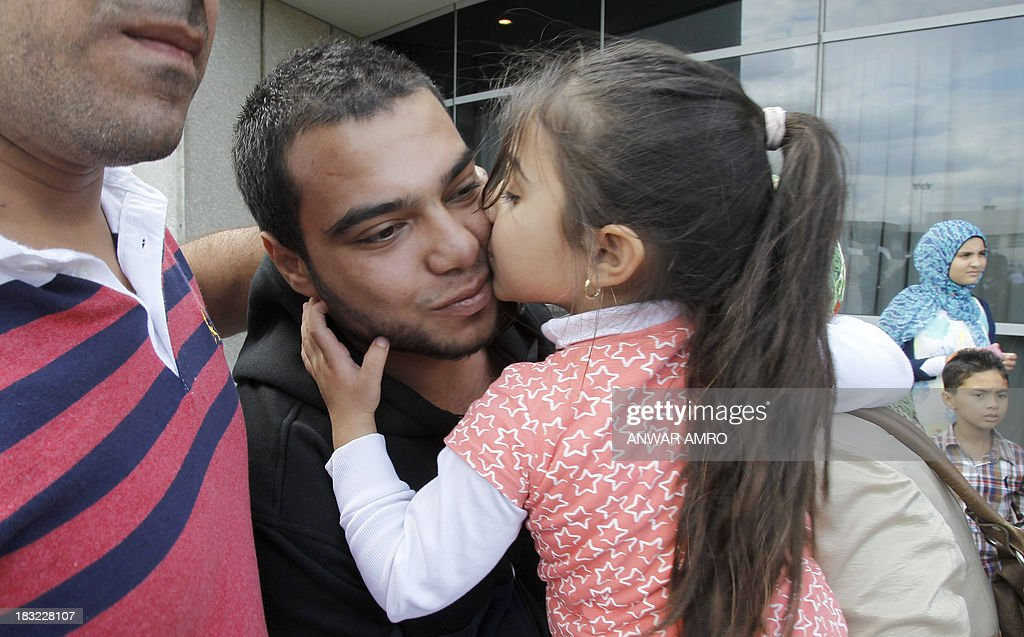 Mahmoud Bahri (L), a Lebanese survivor of the migrant shipwreck in Indonesia last week, is kissed by a relative as he arrives at Beirut airport on October 6, 2013. Lebanese asylum-seekers who died when a boat sank off Indonesia were the victims of people smugglers who prey on them and Syrian refugees seeking to better their lives.