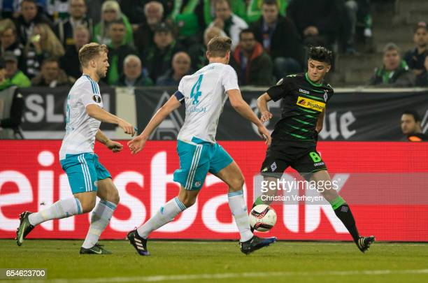 Mahmoud Dahoud of Borussia Moenchengladbach is chased by Benedikt Hoewedes and Johannes Geis of FC Schalke 04 during the UEFA Europa League match...
