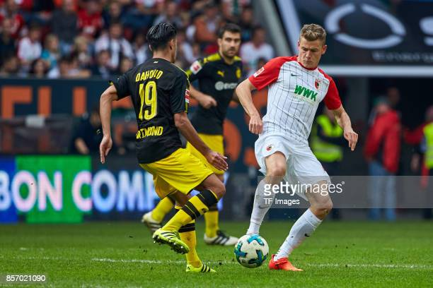 Mahmoud Dahoud of Dortmund and Alfred Finnbogason of Augsburg battle for the ball during the Bundesliga match between FC Augsburg and Borussia...