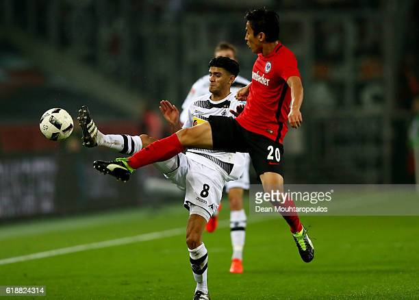 Mahmoud Dahoud of Gladbach and Makoto Hasebe of Frankfurt battle for the ball during the Bundesliga match between Borussia Moenchengladbach and...