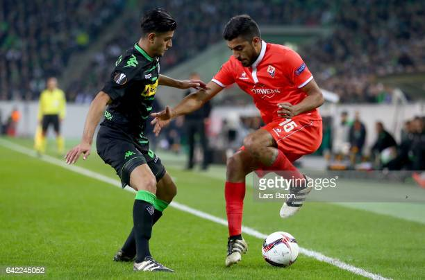 Mahmoud Dahoud of Moenchegladbach challenges Maximiliano Olivera of Fiorentina during the UEFA Europa League Round of 32 first leg match between...