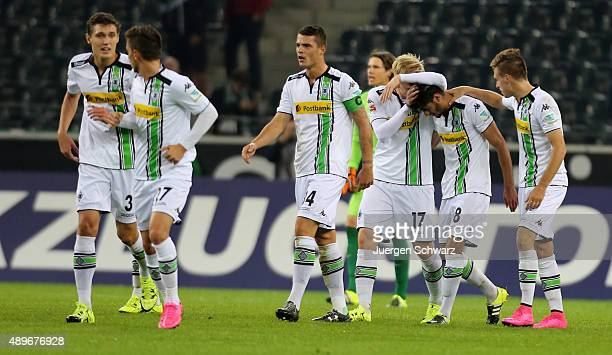 Mahmoud Dahoud of Moenchengladbach is hugged by Patrick Herrmann and Oscar Wendt after scoring during the Bundesliga match between Borussia...