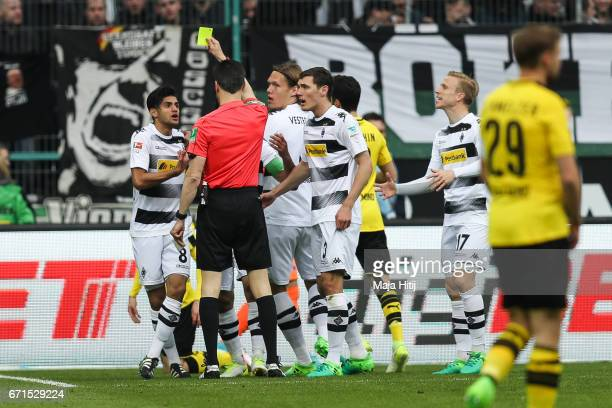 Mahmoud Dahoud of Moenchengladbach is snown a yellow card by referee during the Bundesliga match between Borussia Moenchengladbach and Borussia...