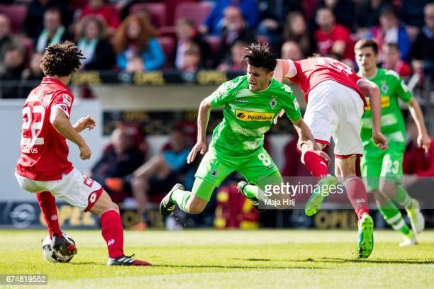 Mahmoud Dahoud of Moenchengladbach Stefan Bell of Mainz and Andre Ramalho of Mainz battle for the ball during the Bundesliga match between 1 FSV...