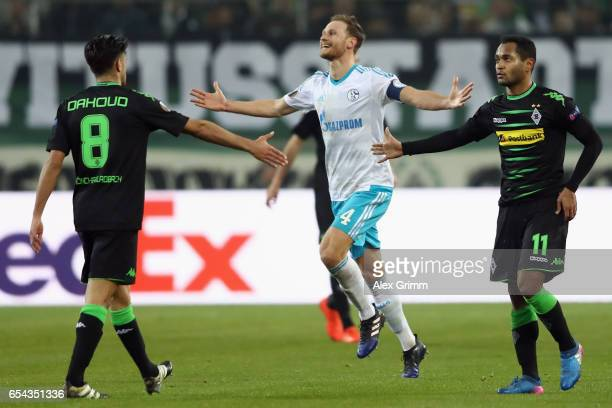 Mahmoud Dahoud Raffael of Moenchengladbach and Benedikt Hoewedes of Schalke react during the UEFA Europa League Round of 16 second leg match between...