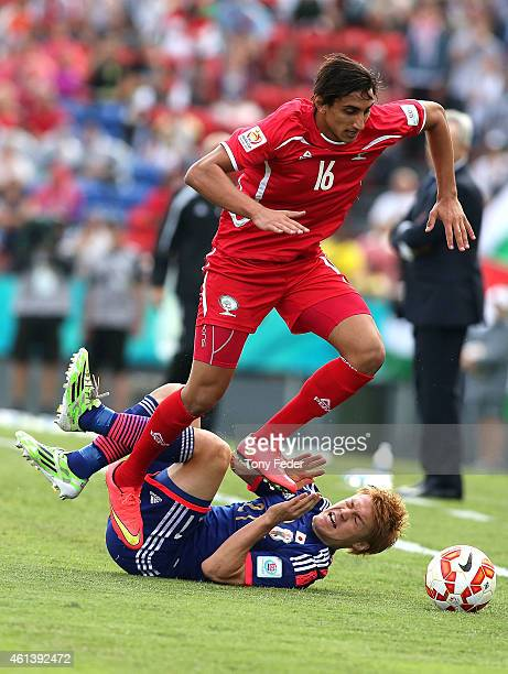 Mahmoud Dhadha of Palestine jumps over Gotoku Sakai of Japan during the 2015 Asian Cup match between Japan and Palestine at Hunter Stadium on January...