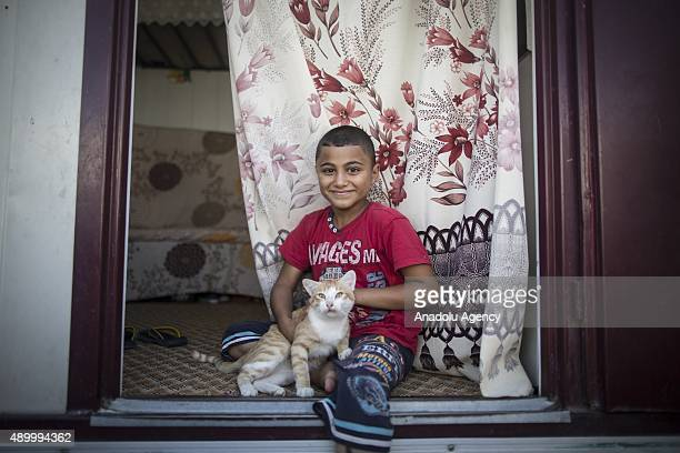 Mahmut Elhatif a Syrian refugee boy who fled Syria with his family poses with his pet cat that he brought from his country at a tent city in the...