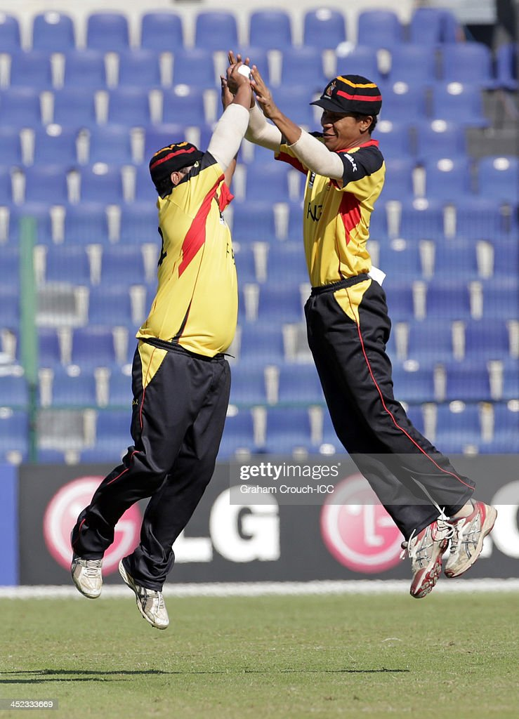 Mahuru Dai (left) of PNG celebrates taking a catch to dismiss Nizakat Khan of Hong Kong during the Quarter Final match 64 between Papua New Guinea and Hong Kong at the ICC World Twenty20 Qualifiers at the Zayed Cricket Stadium on November 28, 2013 in Abu Dhabi, United Arab Emirates.