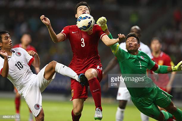 Mai Fang of China tussles for the ball against goalkeeper Yapp Hung Fai of Hong Kong during their 2018 World Cup football qualifying match in...