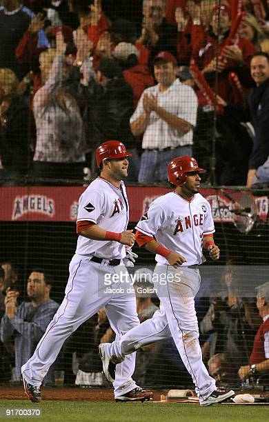 Maicer Izturis and Mike Napoli of the Los Angeles Angels of Anaheim score on a triple hit by Erick Aybar in the seventh inning against the Boston Red...