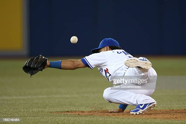 Maicer Izturis of the Toronto Blue Jays cannot handle a throwing error by Munenori Kawasaki in the eighth inning during MLB game action against the...