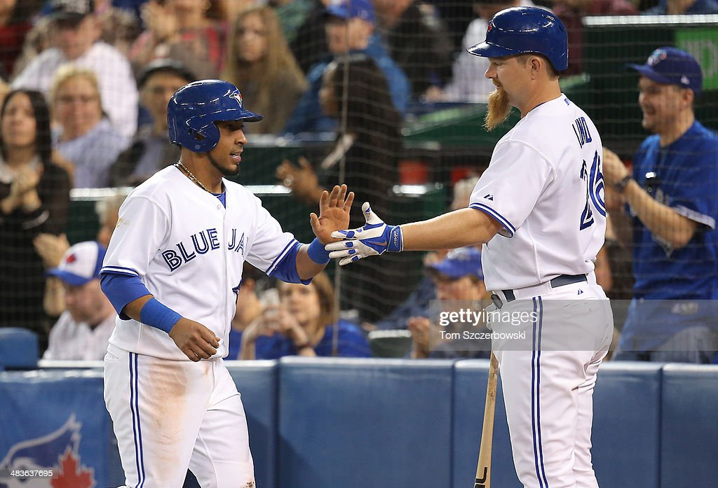 Maicer Izturis #3 of the Toronto Blue Jays is congratulated by Adam Lind #26 after scoring a run in the first inning during MLB game action against the Houston Astros on April 9, 2014 at Rogers Centre in Toronto, Ontario, Canada.