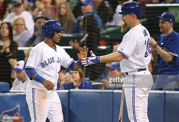 Maicer Izturis of the Toronto Blue Jays is congratulated by Adam Lind after scoring a run in the first inning during MLB game action against the...